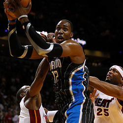 March 3, 2011; Miami, FL, USA; Orlando Magic center Dwight Howard (12)rebounds over Miami Heat center Erick Dampier (25) and shooting guard Dwyane Wade (3) during the first quarter at the American Airlines Arena.    Mandatory Credit: Derick E. Hingle