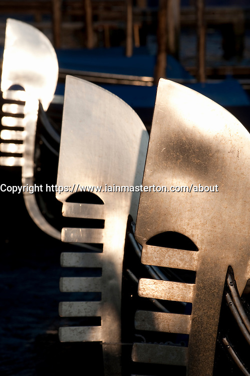 Evening sun reflecting off steel prows of Gondolas moored on Grand Canal in Venice Italy