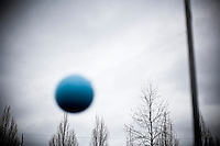 A blue tether ball in a schoolyard with a gray sky.