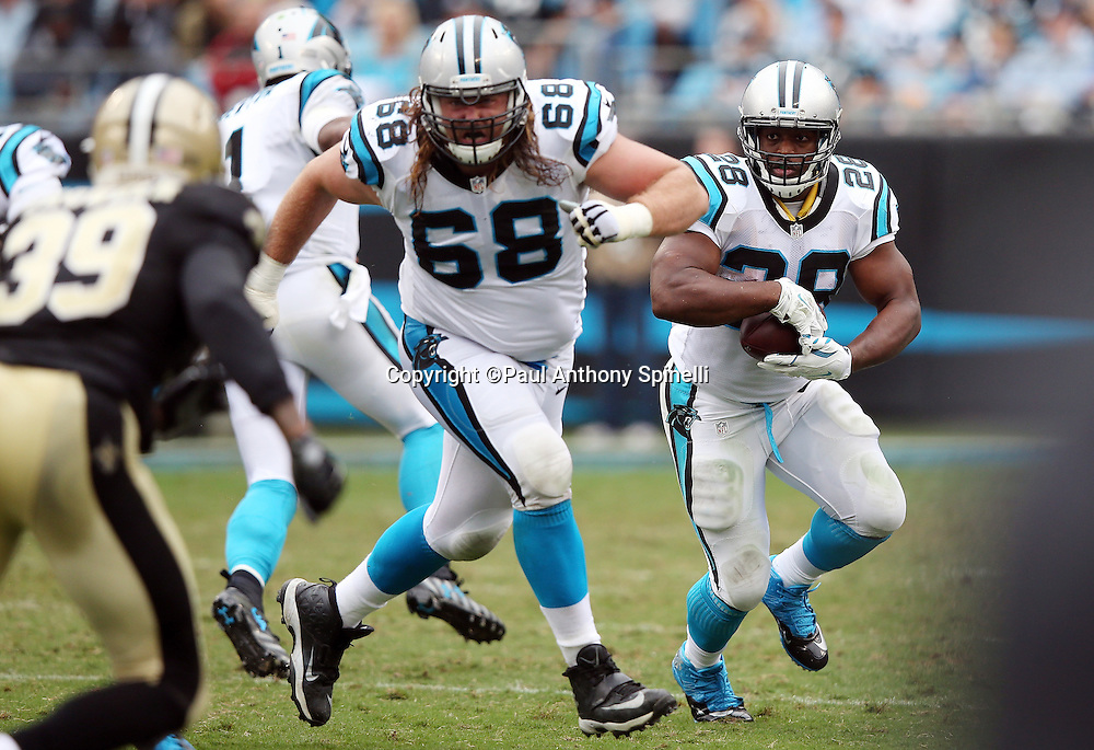Carolina Panthers running back Jonathan Stewart (28) runs the ball behind a lead block by Carolina Panthers guard Andrew Norwell (68) during the 2015 NFL week 3 regular season football game against the New Orleans Saints on Sunday, Sept. 27, 2015 in Charlotte, N.C. The Panthers won the game 27-22. (©Paul Anthony Spinelli)
