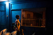 A woman prays while walking the room to comfort her child during a Wednesday evening service at Christ Embassy church, in the Badia neighborhood of Lagos, Nigeria, September 4, 2013. Many here find solace in church, and services can be found every night of the week in the neighborhood.