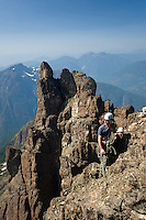 Two climbers ascending the NorthWest ridge of Elkhorn pause to glance at the scenery in Strathcona Park.  Elkhorn Mountain, Strathcona Park, Central Vancouver Island