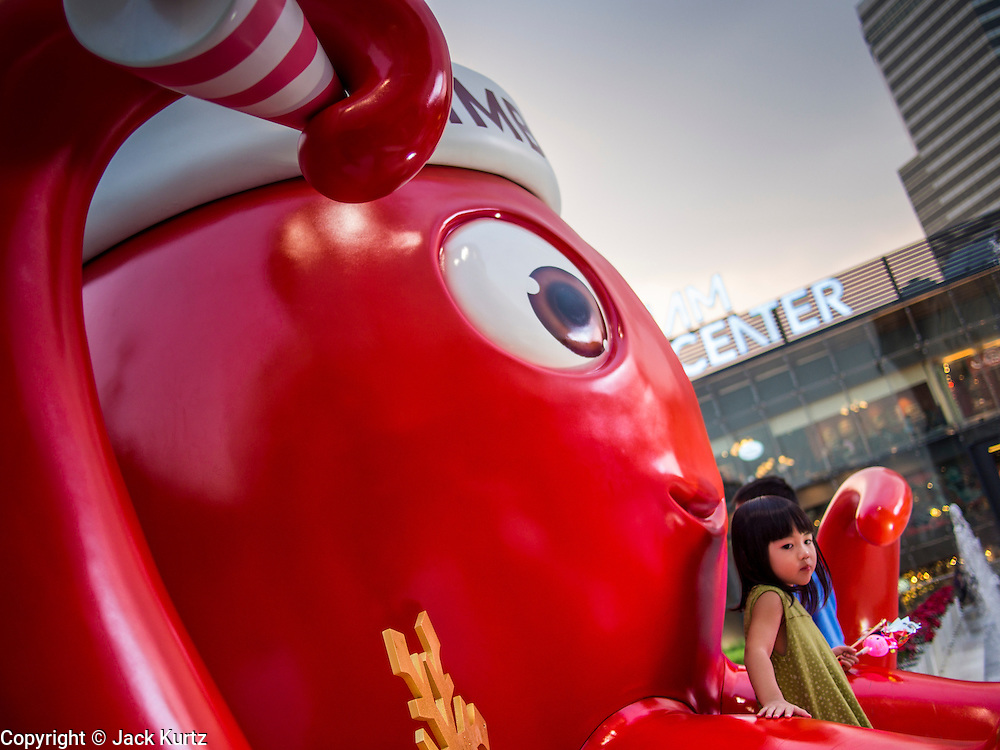 13 DECEMBER 2013 - BANGKOK, THAILAND: A child sits on an octopus wearing a Christmas hat in Christmas display at Siam Paragon shopping center in the Ratchaprasong area of Bangkok. Thailand is overwhelmingly Buddhist. Christmas is not a legal holiday in Thailand, but Christmas has become an important commercial holiday in Thailand, especially in Bangkok and communities with a large expatriate population.      PHOTO BY JACK KURTZ