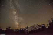The Milky Way is just east of Mt Rainier at 11:30PM. The lights on Mt Rainier are a base camp and the climbers beginning to start their final ascent.  They have a 4,000 foot climb from base camp and try to reach the summit by day break so they can start down before the warm temperatures open crevasses. A meteor glows through the east side of the Milky Way.