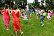 Old Westbury, New York, USA. 28th June 2015. Old Westbury, New York, USA. 28th June 2015. Lori Belilove & The Isadora Duncan Dance Company, wearing colorful Renaissance themed tunics, give Maypole Dance lessons to children on the South Allee of historic Old Westbury Gardens, a Long Island Gold Coast estate, for its Midsummer Night event.
