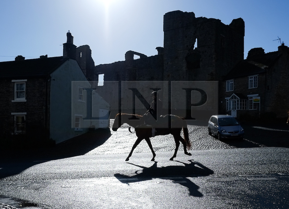 © Licensed to London News Pictures. 22/03/2014<br /> <br /> Middleham, North Yorkshire<br /> <br /> A race horse and rider make their way past Middleham Castle at first light in Middleham, North Yorkshire. Race horses have been trained in Middleham for over 200 years using the extensive gallops on the high moor. There are currently 15 stables based around the small Yorkshire village.<br /> <br /> Photo credit : Ian Forsyth/LNP