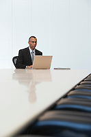 Business man using laptop in board room