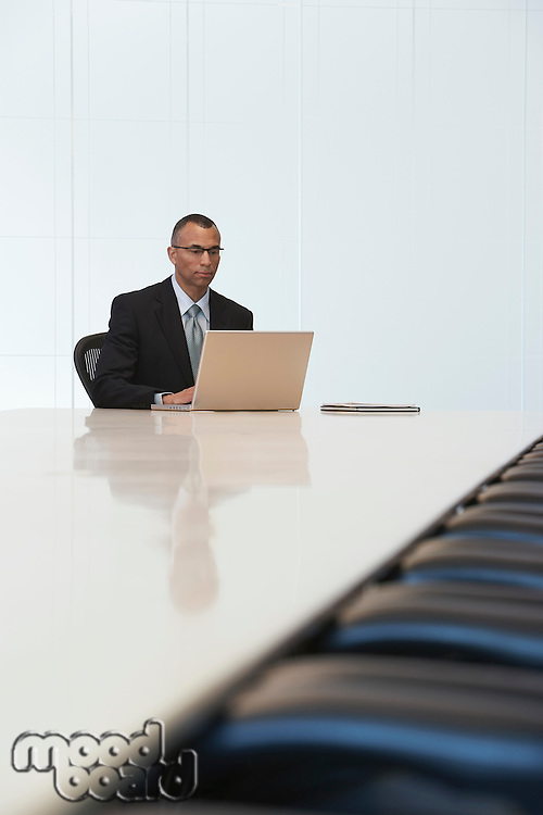 Business man using laptop in board room