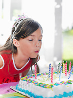 Young girl (7-9) blowing out birthday candles close-up