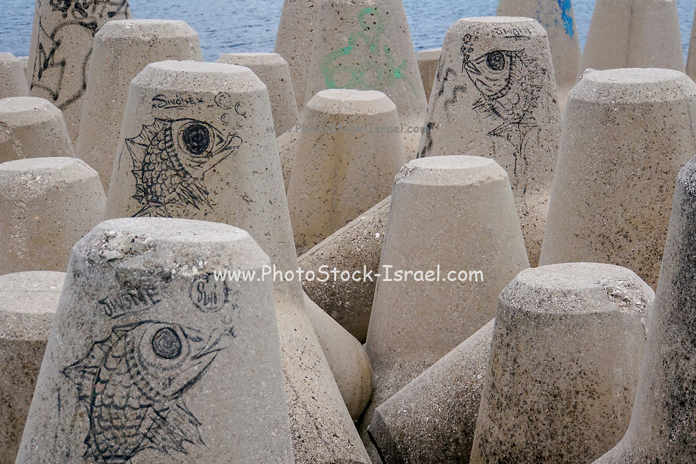 Graffiti on concrete sea wall blocks. Photographed in Athens, Greece