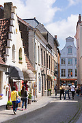 Tourists sightseeing in Walstraat shopping street in Bruges, Belgium