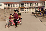 In front of Ren Wang village elementary school, a woman on her electric bike brings her two grand children back home for the lunch break.  In Yicheng County families with a rural hukou (Chinese kind of identity paper) can have as many as two children relaxed version of the one child rule that applies elsewhere in China.