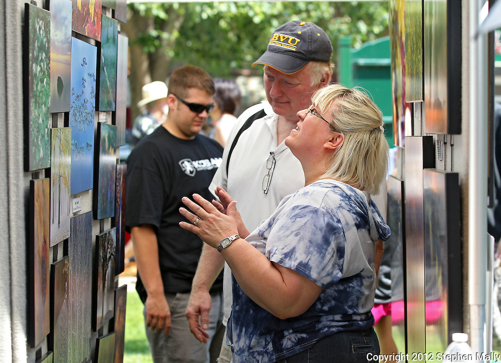 Dan Kearns (from left) and Myra Kearns, of Vinton, talk about the photography prints for sale at a booth during the 20th Annual Marion Arts Festival at City Square Park in Marion on Saturday, May 19, 2012. (Stephen Mally/Freelance)