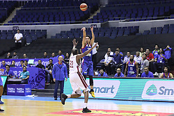 September 17, 2018 - Quezon City, NCR, Philippines - Matthew Wright (Blue) of the Philippines drains a three-pointer over Suliman Abdi Khalid (White)of Qatar. (Photo by Dennis Jerome Acosta/ Pacific Press) (Credit Image: © Dennis Jerome S. Acosta/Pacific Press via ZUMA Wire)