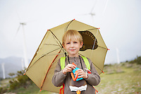 Boy (7-9) with umbrella at wind farm, portrait