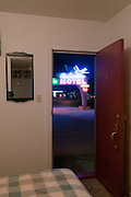 A picture from the inside of a room at the Blue Swallow Motel in Tucumcari, New Mexico looking out at the neon sign. Missoula Photographer