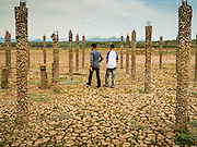 02 APRIL 2016 - NA SAK, LAMPANG, THAILAND: A Thai man and his son walk through the pilings of a structure that used to be in the Buddhist temple in Sobjant village. The village of Sobjant in Na Sak district in Lampang province was submerged when the Mae Chang Reservoir was created in the 1980s. The village was relocated to higher ground a few kilometers from its original site. The drought gripping Thailand drained the reservoir and the foundations of the Buddhist temple in the original village became visible early in 2016. Thai families come down to the original village to pray in the ruins of the temple and look at what's left of the village. This is the first time in more than 30 years that this area has not been under two meters of water.      PHOTO BY JACK KURTZ
