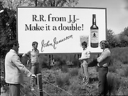 President Reagan Visits Ireland..Advertising Campaign.1984.04.06.1984.06.04.1984.4th June 1984..Availing of the opportunity of the President Reagan visit, the Whiskey manufacturers advertised their wares..Photo shows a large billboard encouraging RR (Ronald Reagan) to have a double. Passers by view the billboard..