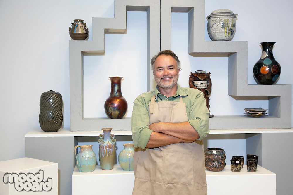 Portrait of a mature potter with arms crossed standing in front of clay vases in workshop