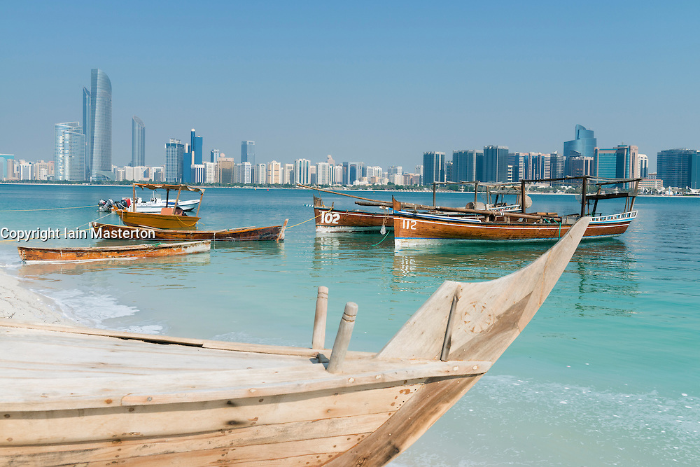 Old fishing boats and skyline of modern skyscrapers on waterfront in Abu Dhabi United Arab Emirates UAE
