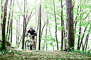 Young man in the 20s mountain biking on a trail on a sunny summer morning.