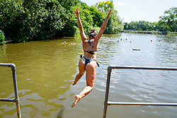 © Licensed to London News Pictures. 05/07/2017. London, UK. Layla Stuart jumps into Hampstead Heath Mixed Bathing Pond in north London as temperatures hit 28C degrees on 5 July 2017. Photo credit: Tolga Akmen/LNP