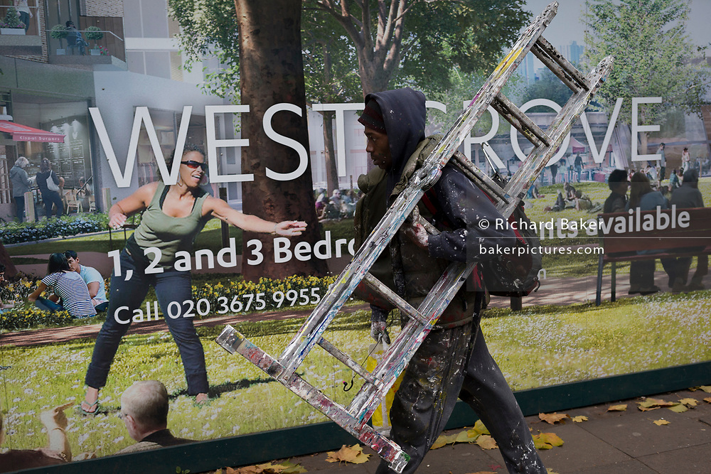 A young workman carries his paint-covered decorating ladders past the construction hoarding for the new West Grove in the Elephant Park development at Elephant & Castle, on 16th November 2017, in London, England.