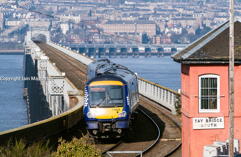 View of Scotrail diesel passenger train travelling to Dundee across the Tay Rail Bridge at Wormit in Tayside, Scotland, United Kingdom