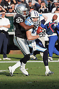OAKLAND, CA - DECEMBER 19:  Wide receiver Drew Bennett #83 (caught 13 passes for 160 yards and 2 touchdowns) of the Tennessee Titans gets tackled by Denard Walker #25 of the Oakland Raiders at Network Associates Coliseum on December 19, 2004 in Oakland, California. The Raiders defeated the Titans 40-35. ©Paul Anthony Spinelli *** Local Caption *** Drew Bennett;Denard Walker