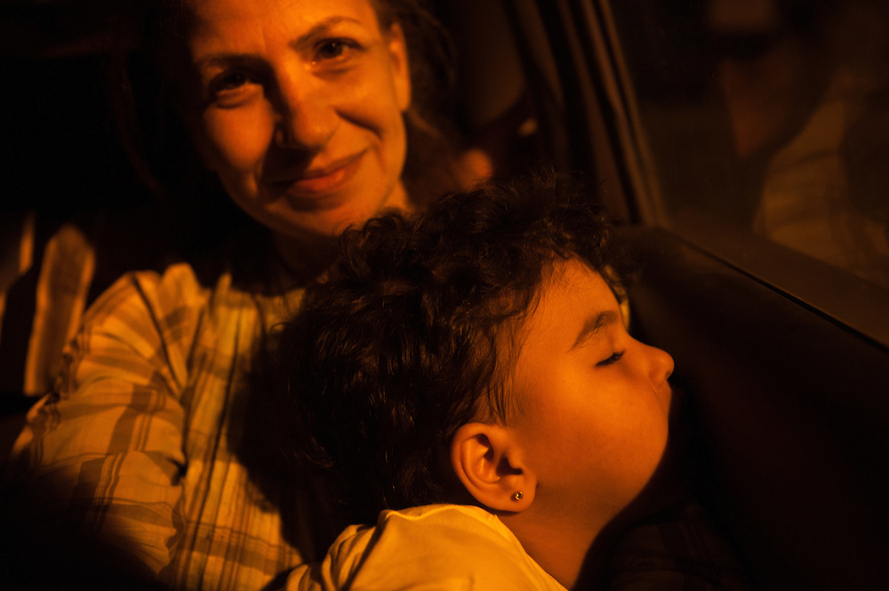 Thursday 10 September 2015 at 20:09 in the village of Mantamados, Lesbos island.  Aysha at the back of my car with her daughter Bisan sleeping in her arms. Aysha was the most vulnerable person of her group so I offered her a lift from the landing spot to the registration camp of Kara Tepe in Mytilini. The rest of her group had to walk to the village of Sikaminia and then either walk the 43 Kilometres to the camp or wait for hours for one of the buses run by MSF, and IRC to take them there.