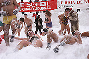 Hypothermia: The annual Snow Bath at the Winter Carnival in Quebec, Canada. Onlookers gather to cheer on these snow bathers. Seventy-five courageous men and women brave the cold. Their only protection: a bathing suit. Three quick dips in the snow interrupted with a short break out of the cold are part of the program. Ice Palace seen in the background. [1988]