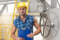 Portrait of confident male worker holding clipboard in industry