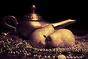 horizontal still life image of two pears, teapot and beads/ coins in golden monochromatic tones