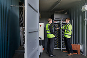 London, England, UK, September 6 2018 - Employees of UPS and UK Power Networks Services discuss in front of onsite energy storage batteries at UPS Central London site.<br /> A UPS led consortium with UK Power Networks Services and Cross River Partnership has deployed a new charging technology in London that overcomes the challenge of simultaneously recharging an entire fleet of electric vehicles (EVs) without the need for the expensive upgrade to the power supply grid. The technology, based on the use of onsite energy storage batteries, is now used to provide extra energy needed during peak hours, but it should also allow to increase the number of EVs operating from UPS central London site from the current limit of 65 to all 170 trucks based there.