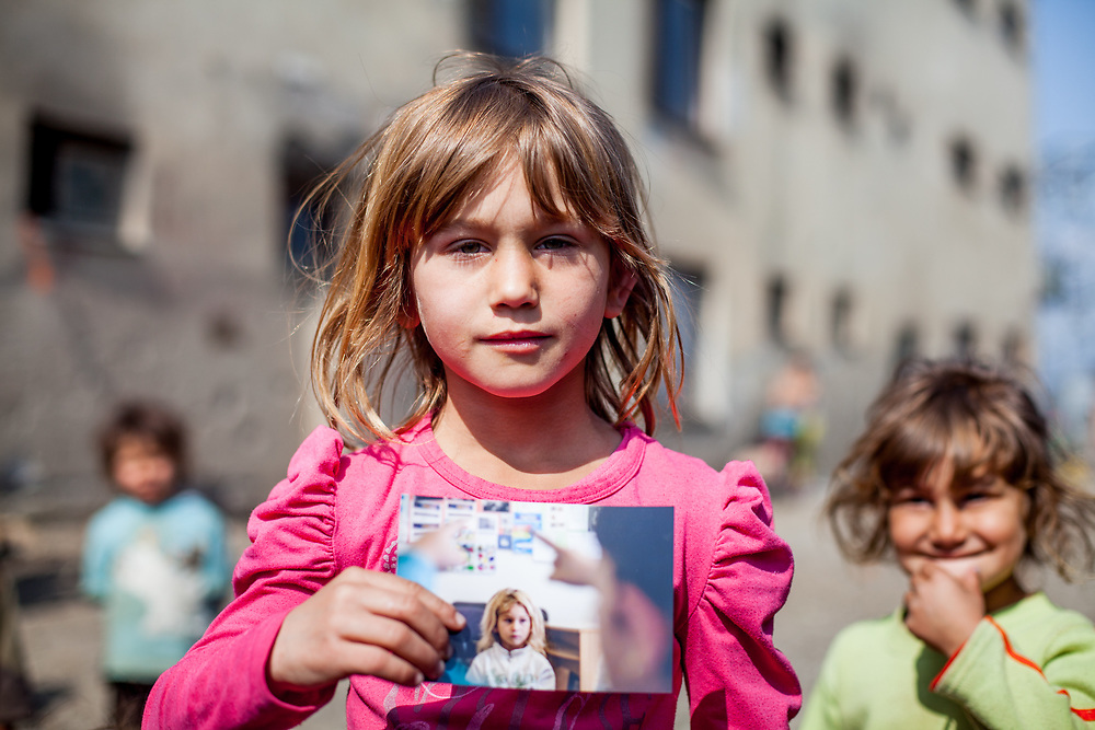 """A gilrl living at the Roma settlement """"Budulovska Street"""" is holding a photograph of herself made two years before. From about 800 inhabitants of the segregated settlement 'Budulovska Street' (2014) are roughly 392 children up to the age of 16 years."""