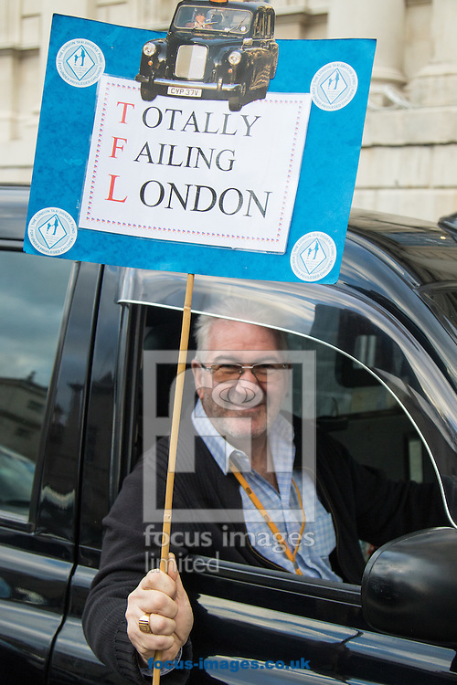 A taxi driver displays his banner as an estimated 8,000 cabbies protest against &quot;unfair competition&quot; from Uber mini cabs<br /> Picture by Paul Davey/Focus Images Ltd +447966 016296<br /> 10/02/2016