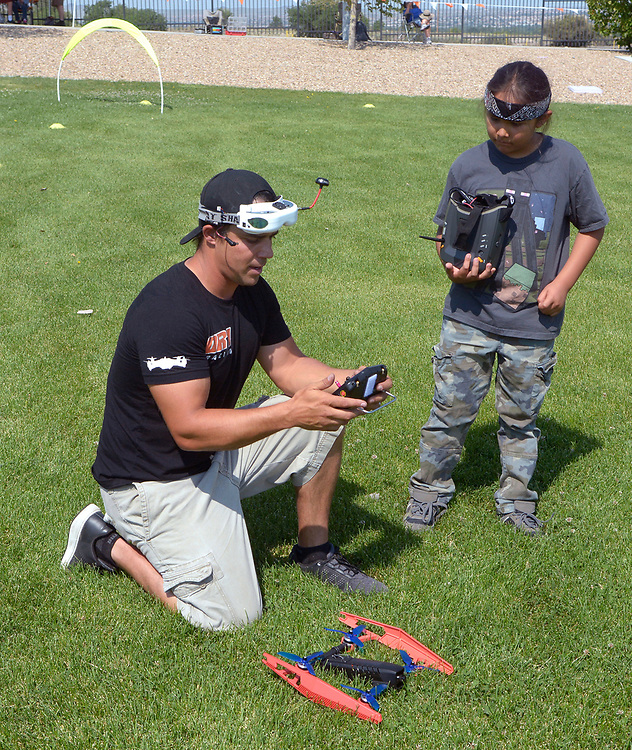 gbs062517h/ASEC - Shaun Taylor, left, with Southwest Pod Racing, sets up Harold Rogers, 8, to fly a drone during the Drone Discovery Day at the Anderson Abruzzo Albuquerque International Balloon Museum on Sunday, June 25, 2017. (Greg Sorber/Albuquerque Journal)