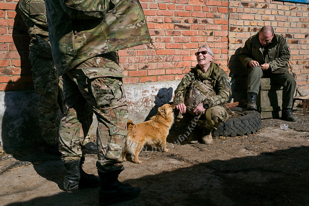Julia Paevska (centre) is talking with other volunteers while caressing a dog in the front-yard of an improvised 'warehouse' for medicines, set up in an abandoned home in the village of Klynove, near the frontline in eastern Ukraine.