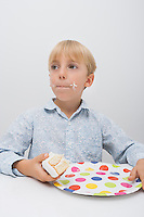 Cute boy with cake slice in plate on table looking away at home