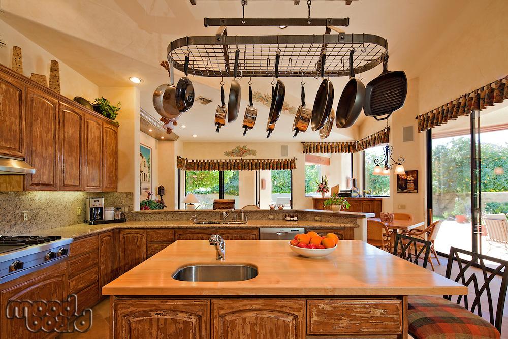Kitchen counter with utensils hanging in luxury villa