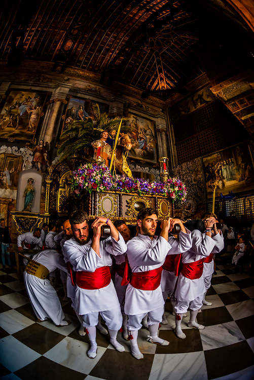 """A paso (float) carried by men called """"costaleros"""" from the Brotherhood (Hermandad) de Nuestro Padre Jesus on Palm Sunday of Holy Week (Semana Santa) is carried into the Convento de Santa Clara at the end of the procession, Loja, Granada Province, Andalusia, Spain."""