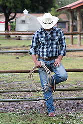 cowboy leaning against a metal fence on a ranch