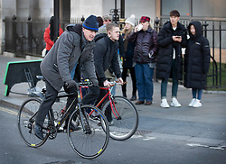 © Licensed to London News Pictures. 28/01/2019. London, UK. Tourists look on as former foreign secretary Boris Johnson (L) cycles to Parliament ahead of crucial votes on Brexit amendments. Photo credit: Peter Macdiarmid/LNP