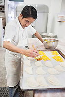 Young male baker working on preparation of pastry in bakery kitchen