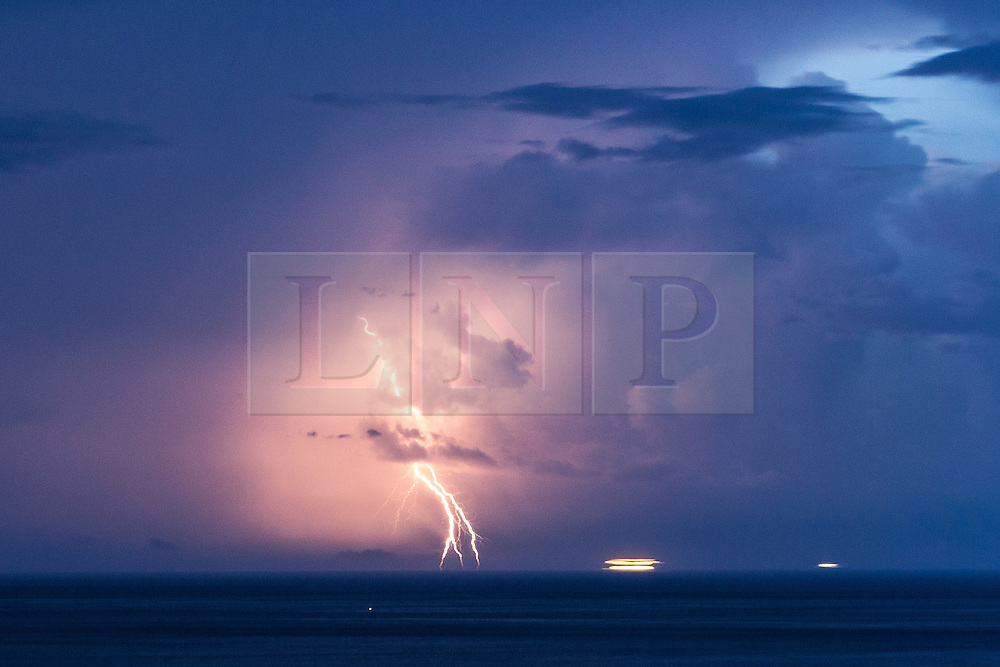 © Licensed to London News Pictures . 03/08/2014 . Cassis , France . A ship passes through a thunderstorm , the sea around struck by bolts of lightning , as intense electrical storms sweep the South of France this morning ( Sunday 3rd August 2014 ) . Viewed from the historic town of Cassis , near to Marseille in the South of France , the vulnerable vessel is seen steaming straight in to the path of the storm in the Mediterranean Sea and , at one point , appears to be struck by lightning . Photo credit : Joel Goodman/LNP
