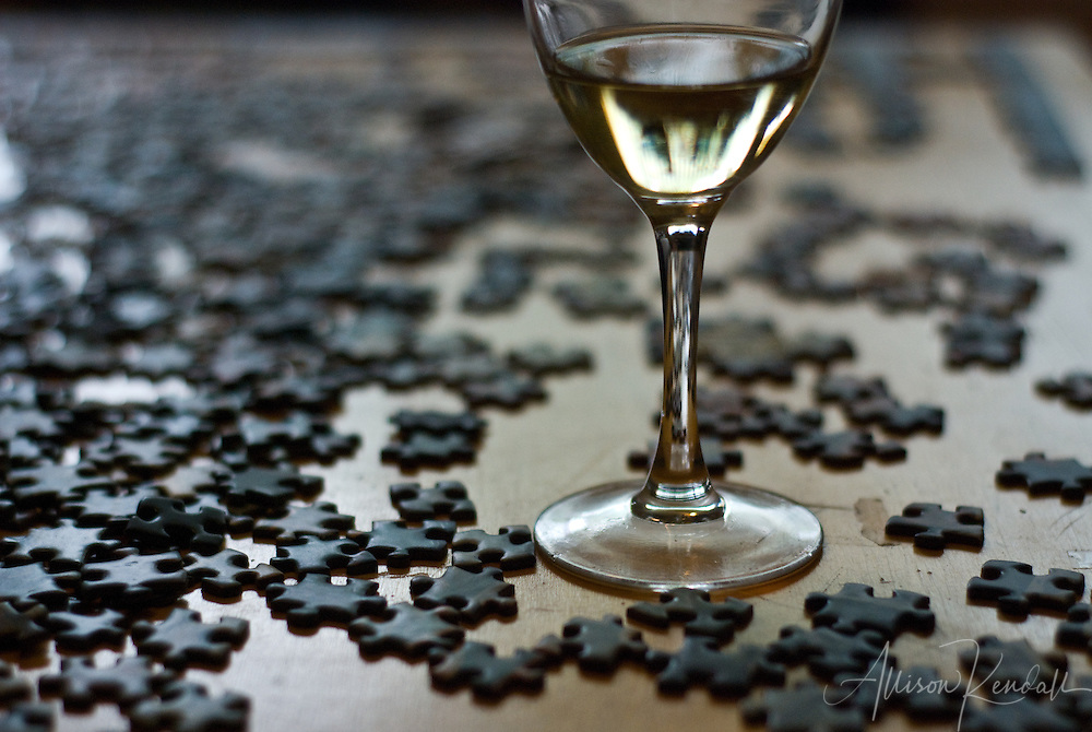 A wineglass sits on a table surrounded by puzzle pieces