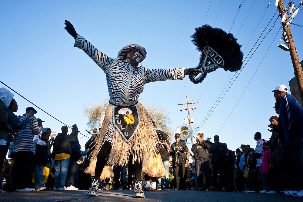 A costumed member of the Zulu Social Aid and Pleasure Club dances in front of a traditional New Orleans brass band in the Krewe of Zulu Parade on Mardi Gras day near Claiborne Avenue in New Orleans, Louisiana, USA.