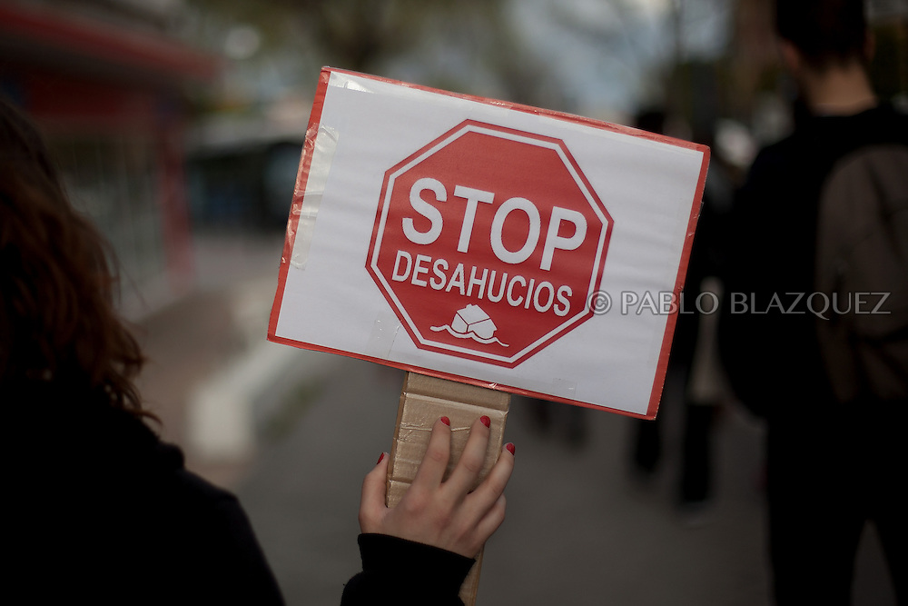 An anti eviction activist holds a placard reading 'Stop evictions' after an 'escrache' outside the house of PP deputy Beatriz Rodriguez Salmones on April12, 2013 in Madrid, Spain. The Mortgage Holders Platform (PAH) and other anti evictions organizations have been organizing 'escraches' for several weeks under the slogan 'There are lives at risk' to claim the vote for a Popular Legislative Initiative (ILP) to stop evictions and facilitate social rent, outside Popular Party deputies' houses and offices. 'Escraches' are a form of peaceful protest that were used in Argentine in 1995 to publically denounce pardoned members of the dictatorship for their crimes at their doorsteps.