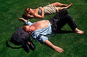 Two 1990s office workers sunbathe on grass during their lunchtime, on the grass in the City of London (aka The Square Mile), the capital's financial centre, on 20th June 1992, in London, England. (Photo by Richard Baker / In Pictures via Getty Images)