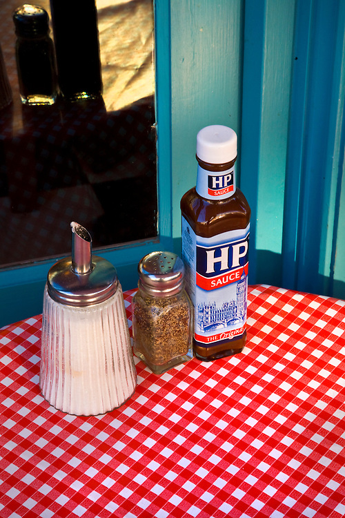 condiments on a red and white tablecloth outside a cafe